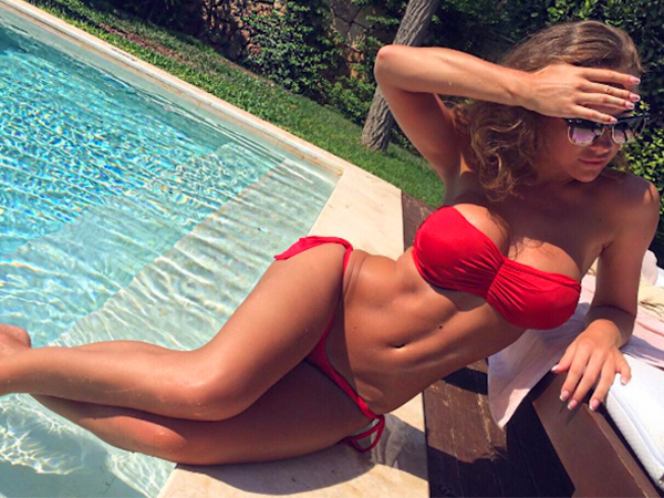 Sexy model in red two piece bikini showing deep cleavage by the pool