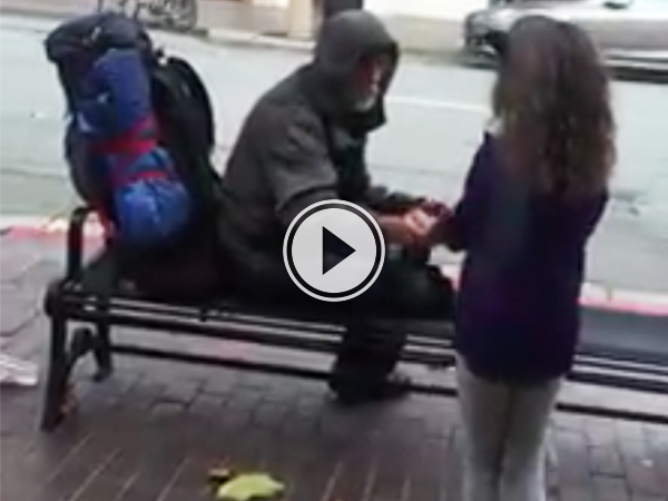 Little girl gives food to homeless man