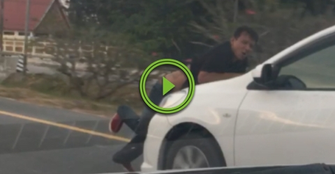 Guy gets stuck on hood of car while driving down road (Video)