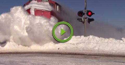 Train obliterates massive snowbank (Video)
