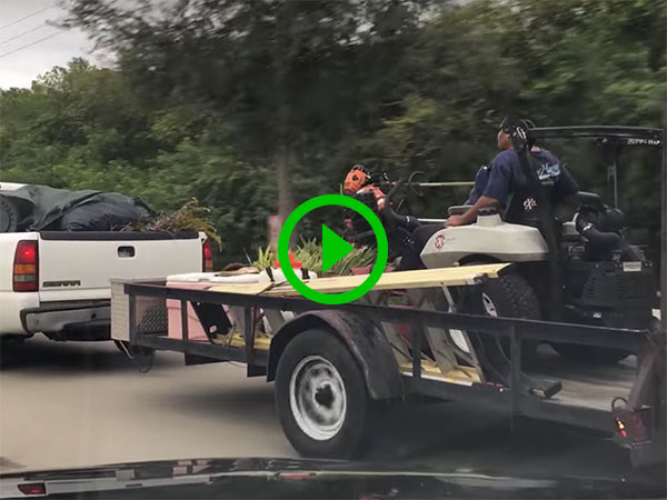 Dude rides on mower hitched to back of truck (Video)