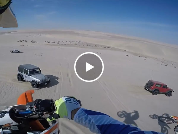 Guy accidentally hits jeep after jumping 100ft off sand dune (Video)