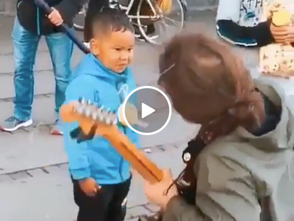 Guitarist's working hard to get that kid's smile (Video)